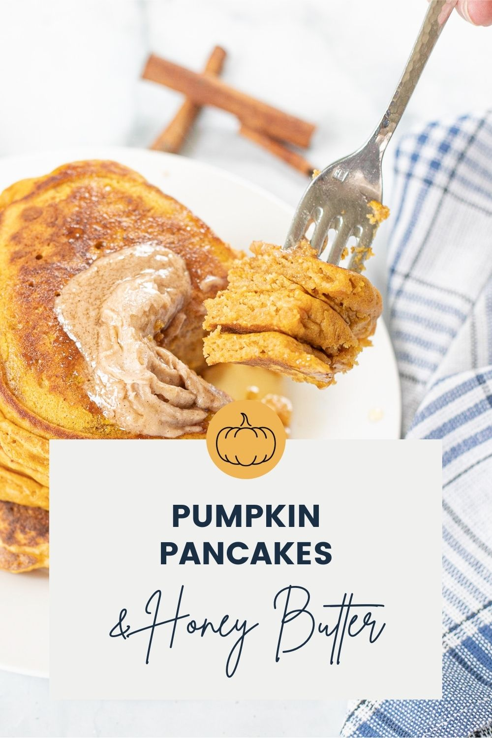 Forkfull of pancakes over a plate of pumpkin pancakes.