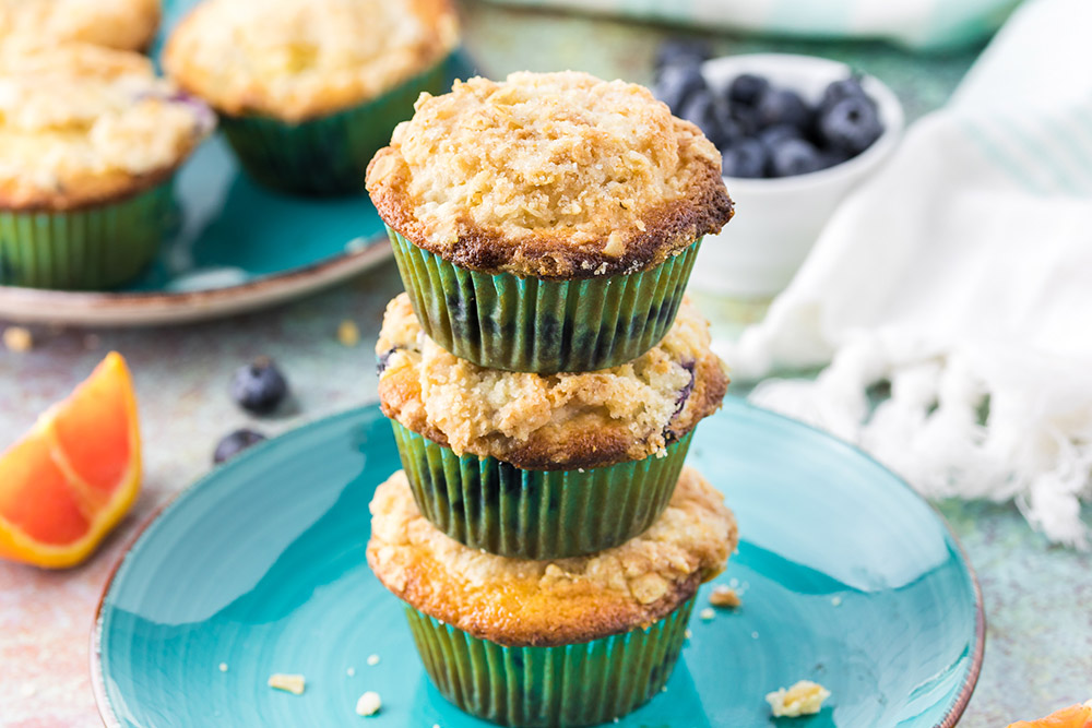Three muffin stacked on top of each other on a blue plate.