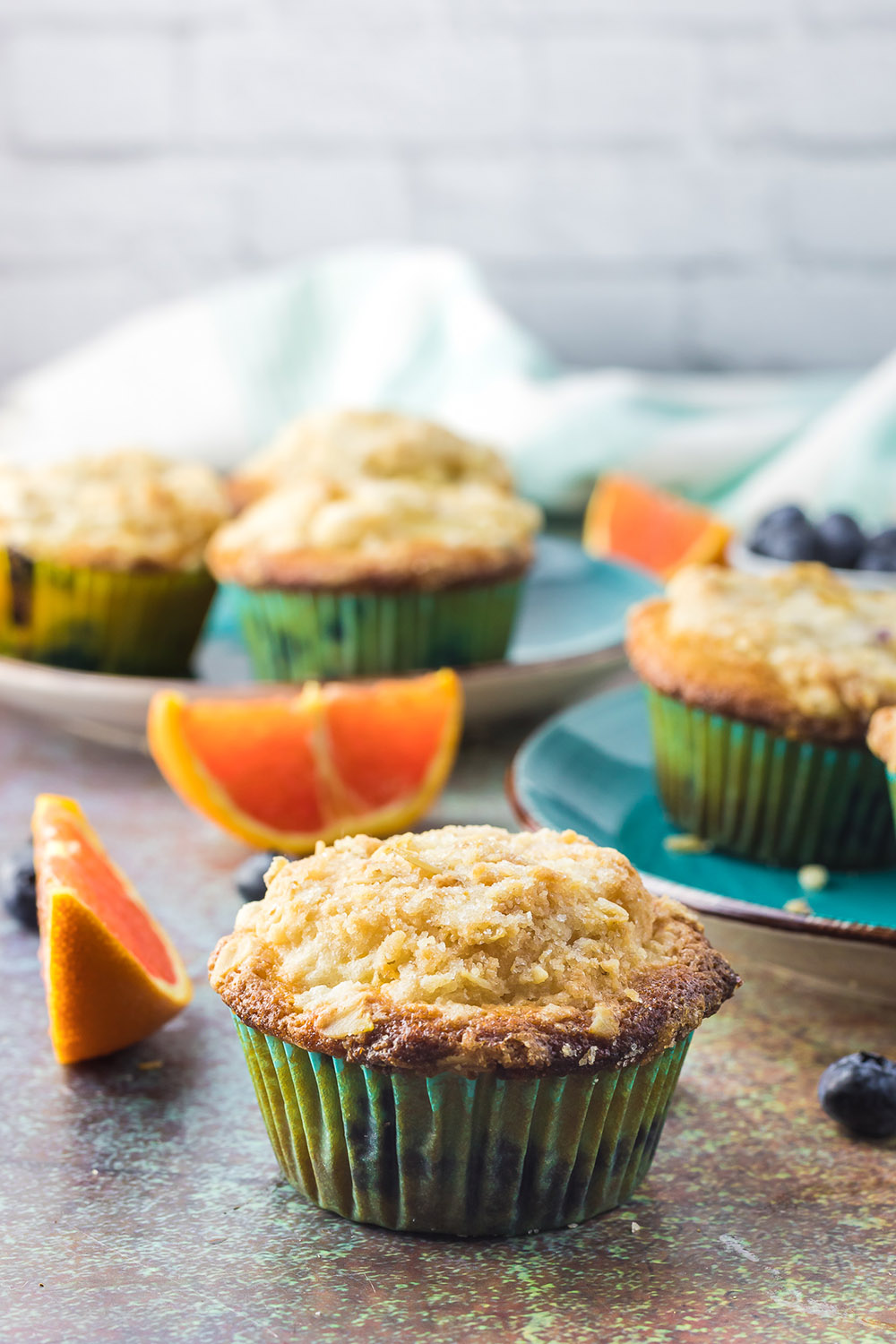 Blueberry muffins on a table with orange slices.