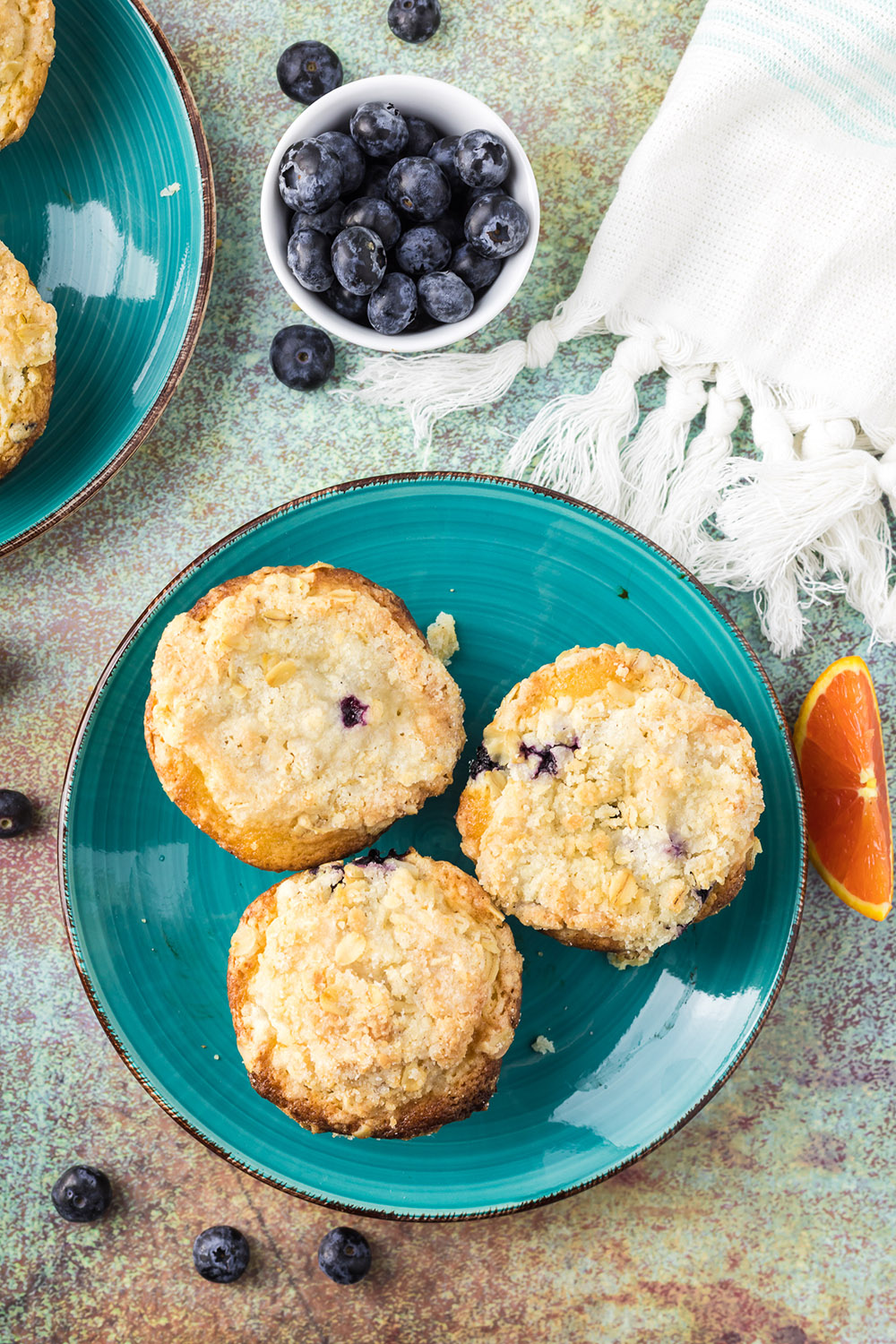 Overhead image of three blueberry muffins on a blue plate.