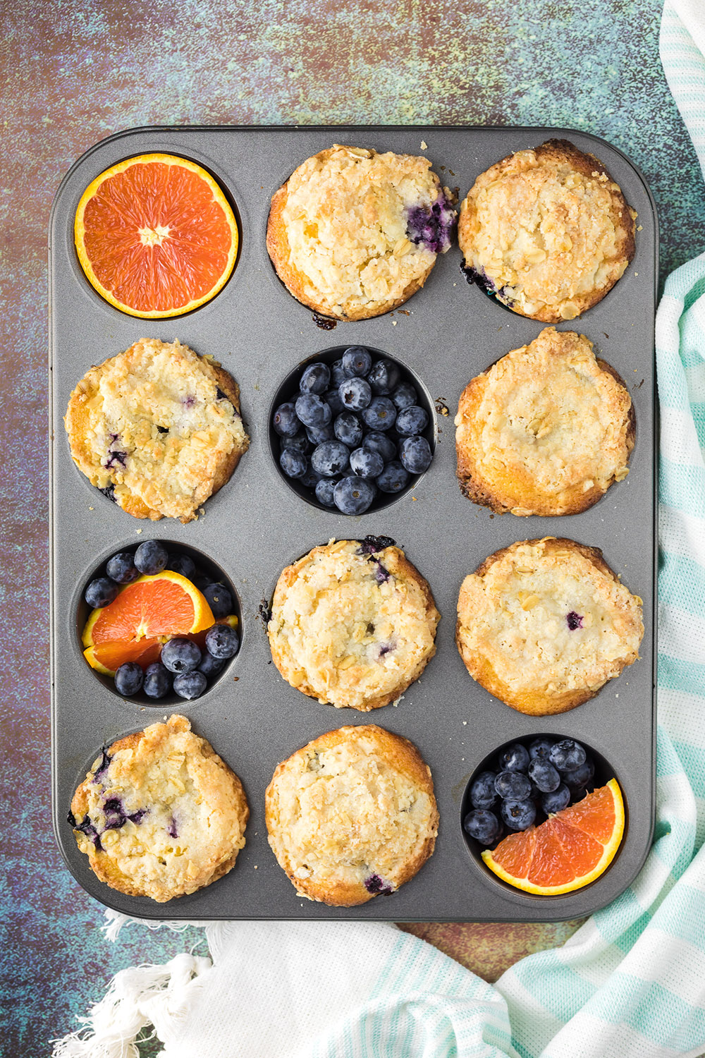Muffin tin with muffins, oranges, and blueberries in it.
