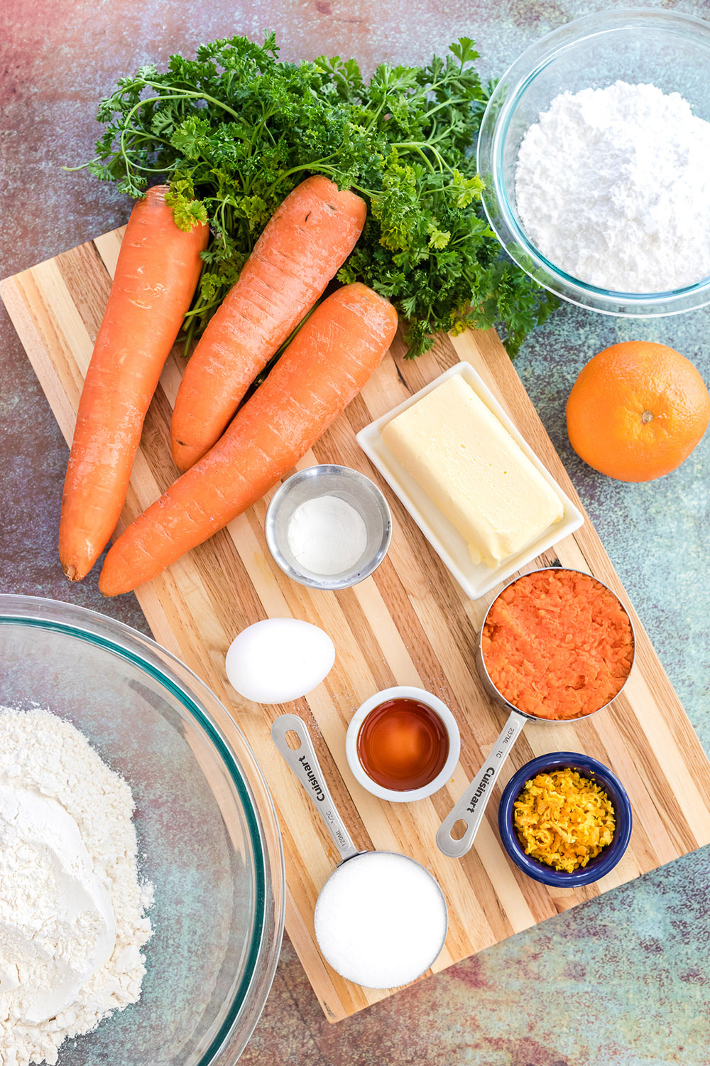 Carrots, sugar, flour, and other ingredients on a board.