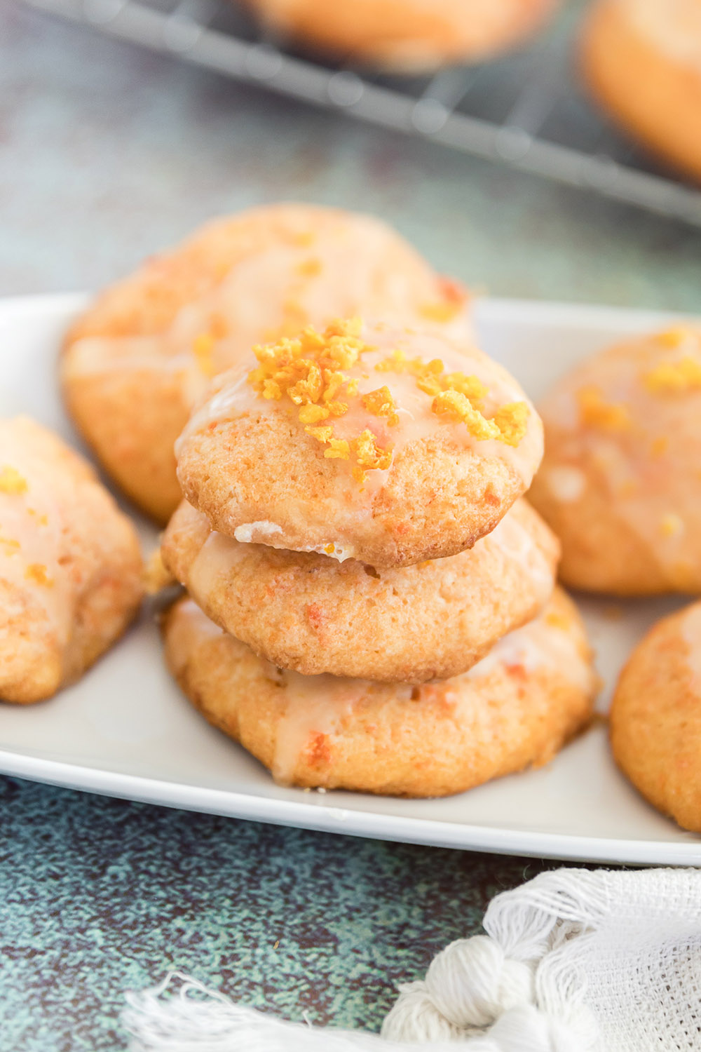 Stacked cookies on a tray. The cookies have a carrot glaze and are orange in color.