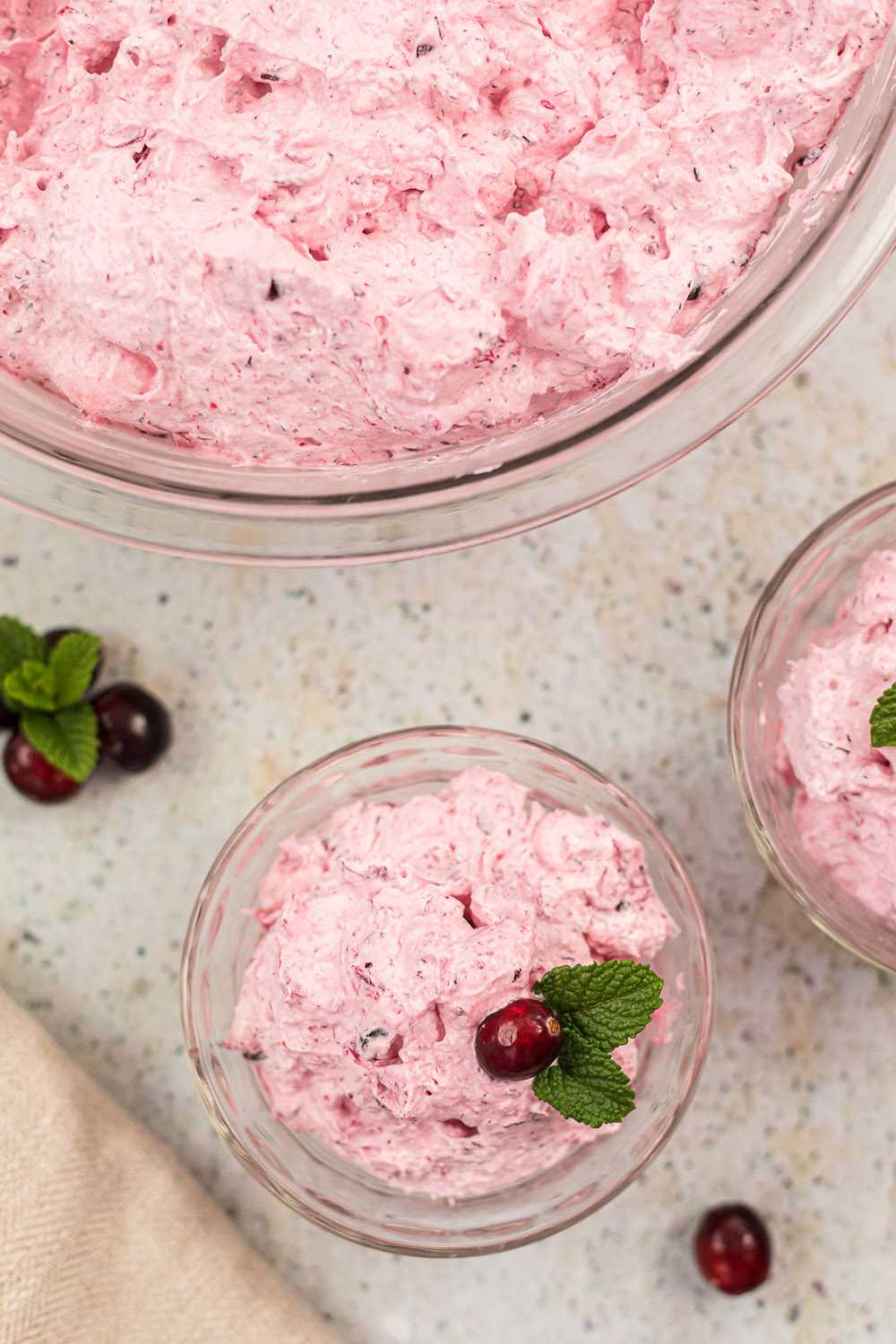 Clear bowls filled with pink whipped cranberry salad.