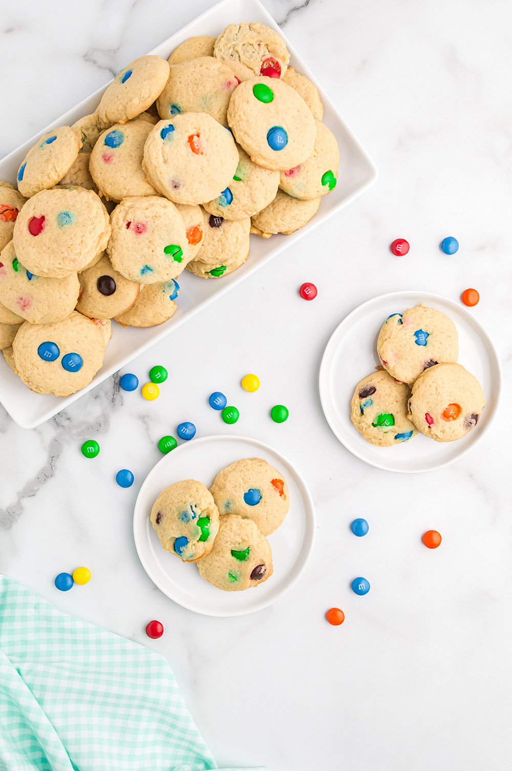 Overhead image of cookies on plates and on a tray with M&M's sprinkled on the table.
