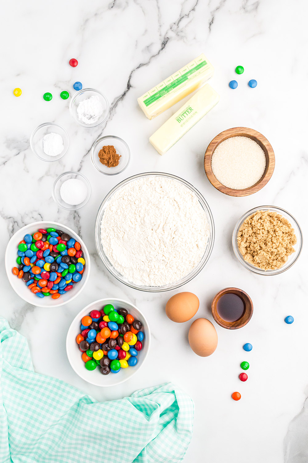 Butter, flour, M&M candies, eggs, and other ingredients to make cookies.