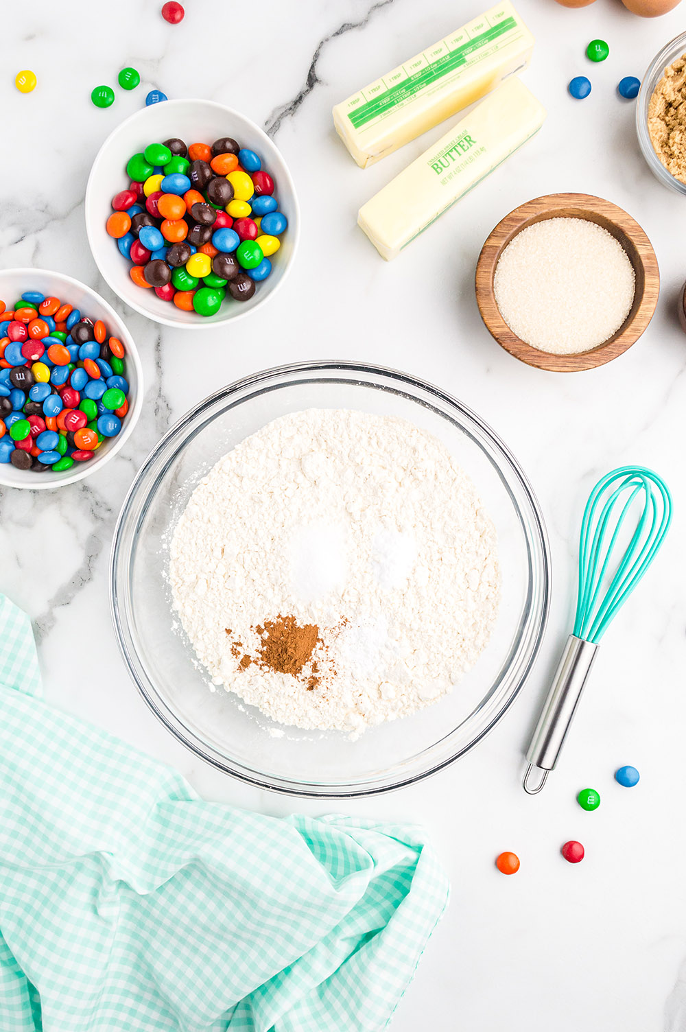 Bowls of ingredients to make M&M cookies.