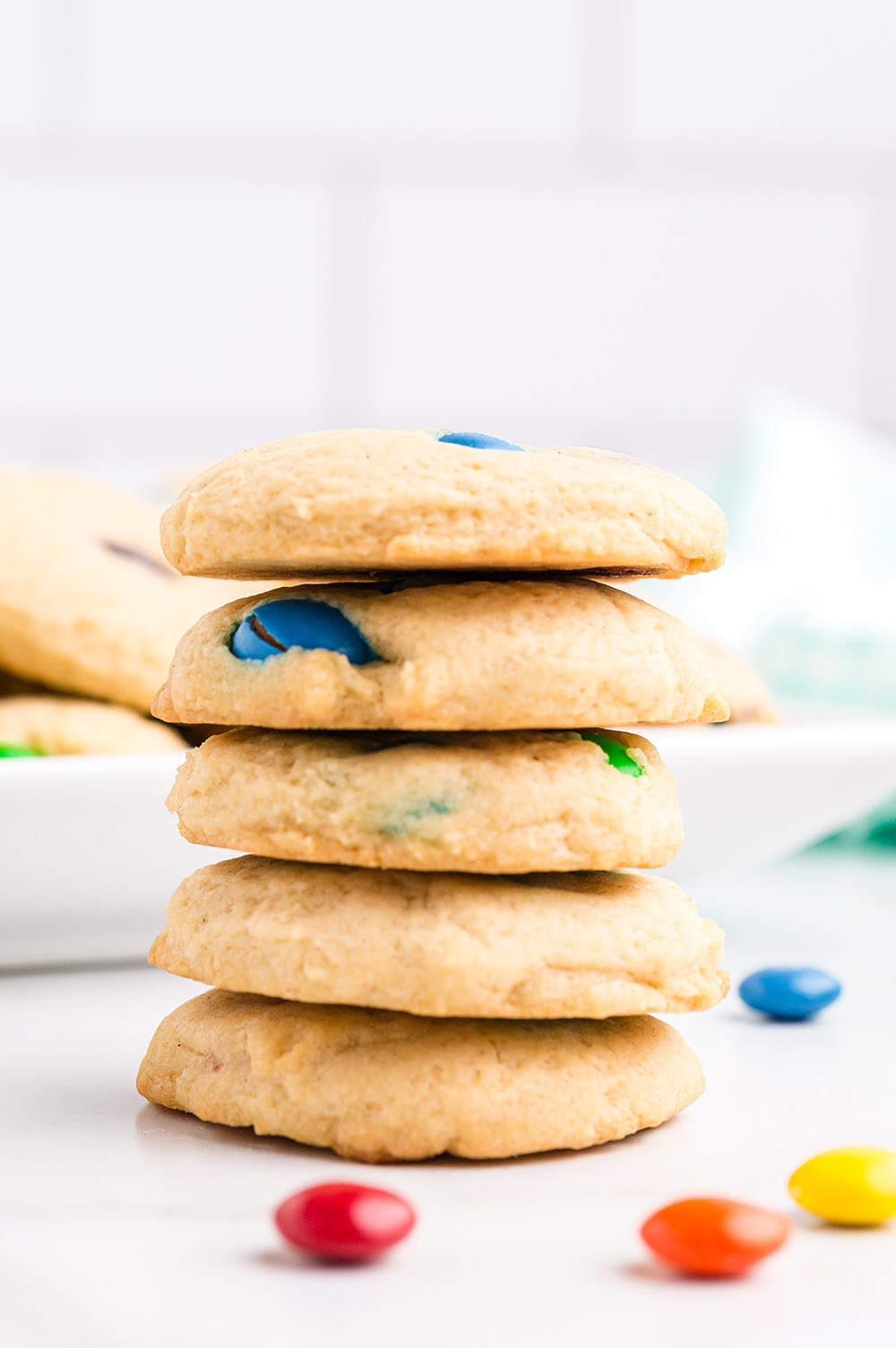 Stack of cookies with M&M candies on the table.