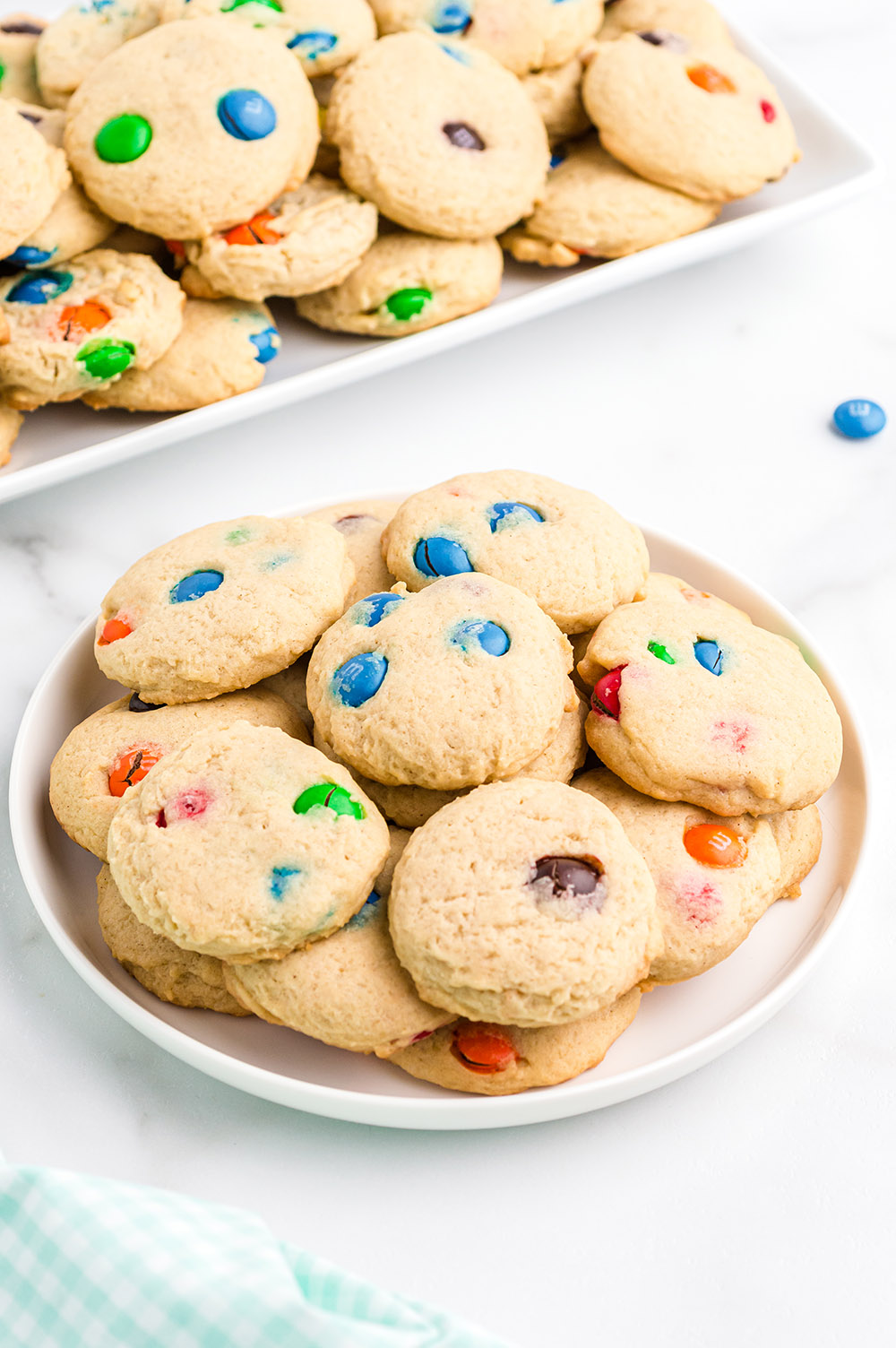 Plate of cookies with more on a tray in the background.