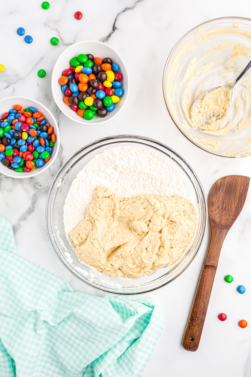 Mixing ingredients together for M&M cookies.