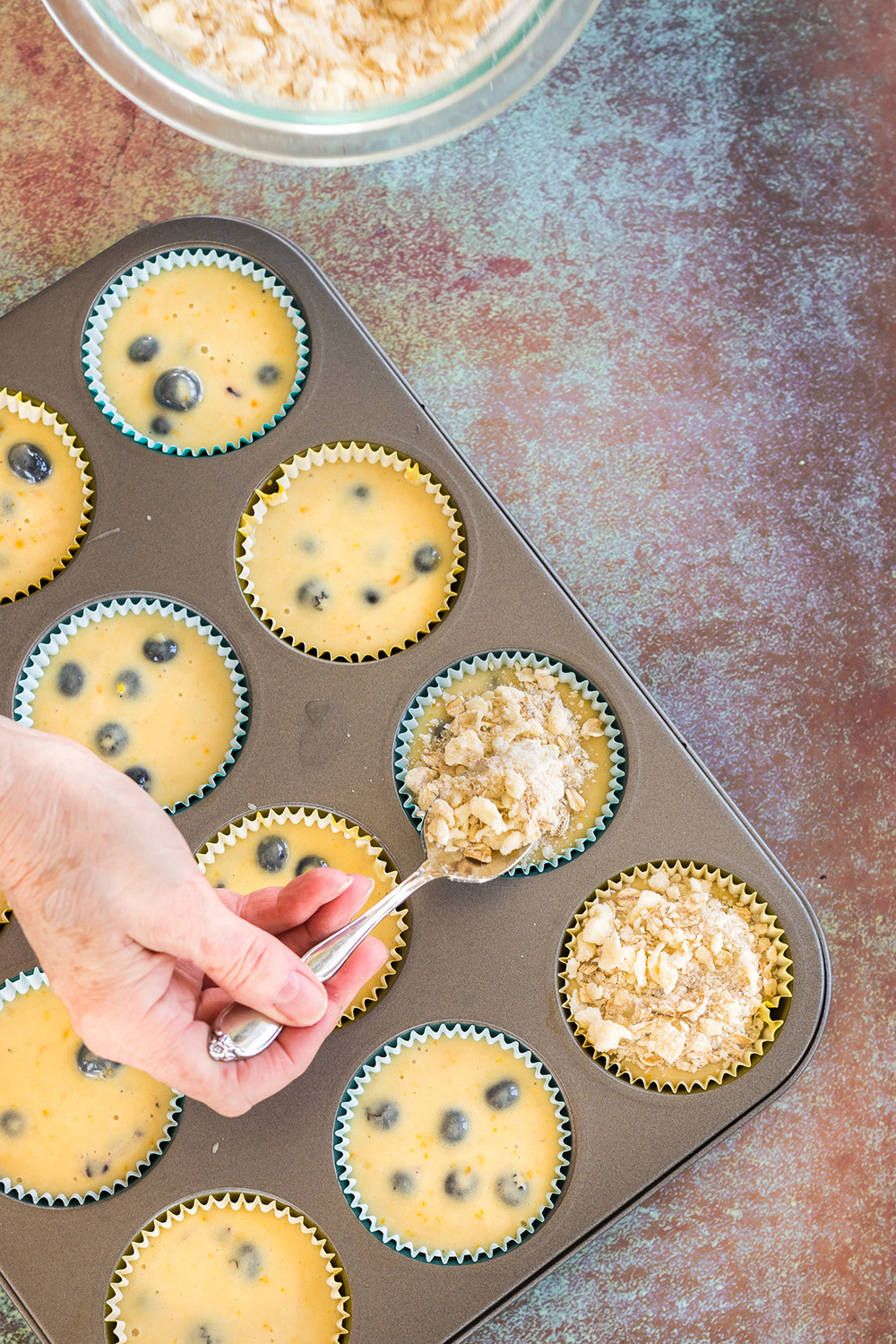 Adding topping to blueberry muffins in a tin.