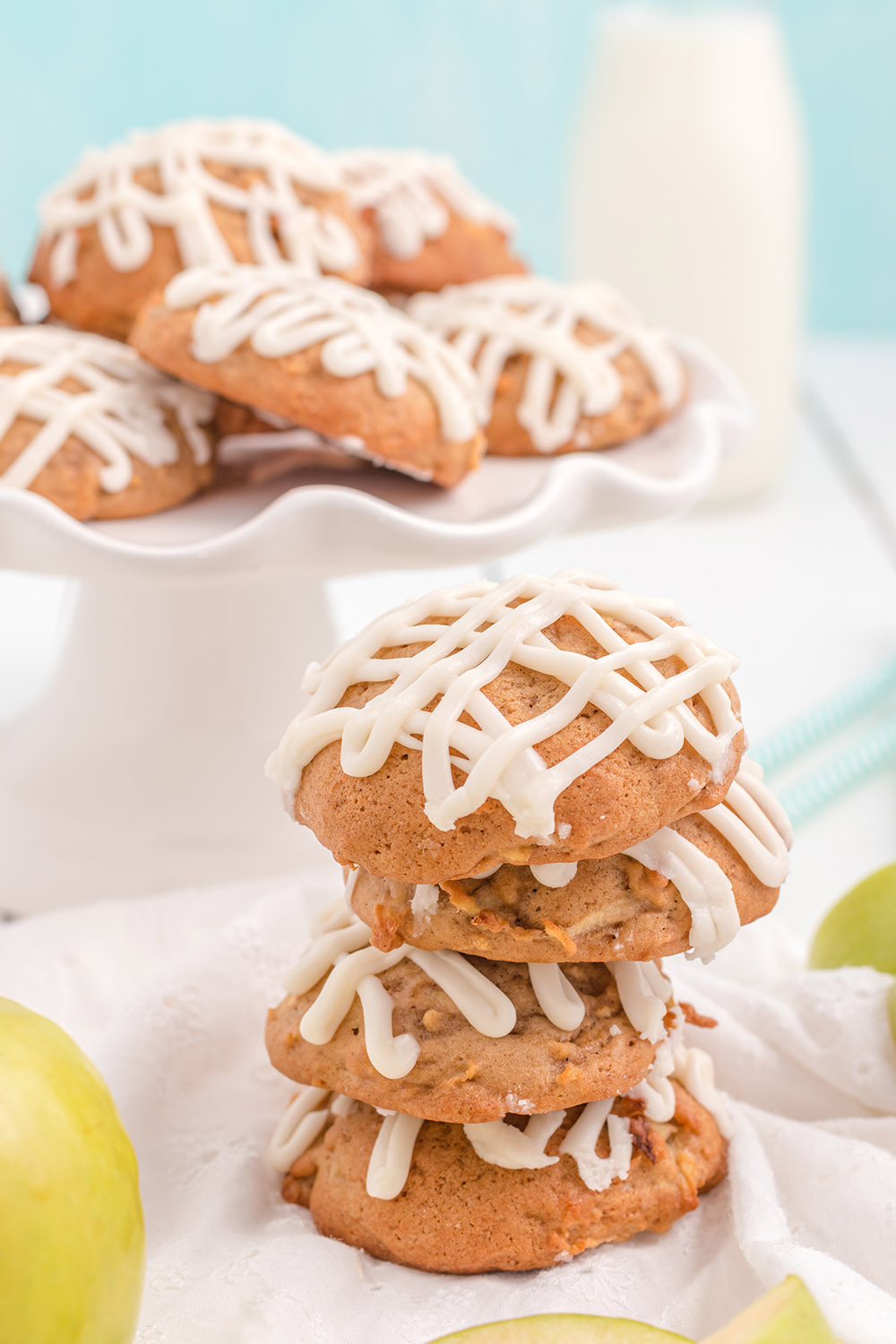 Cookies in a stack and on a tray with milk and apples.