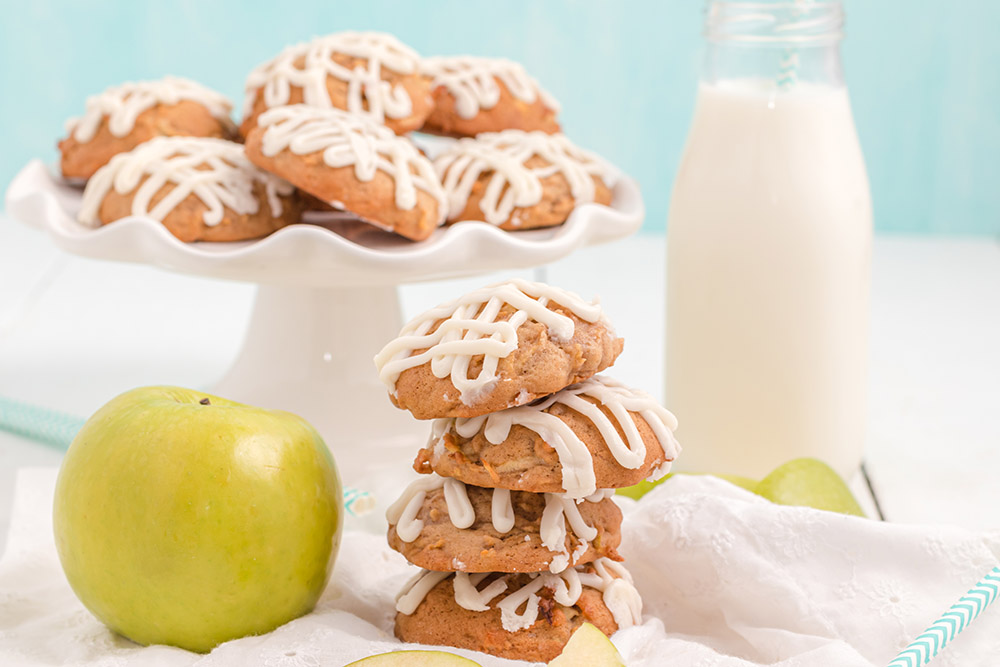 Stacked apple cookies next to a green apple and a plate of more cookies.