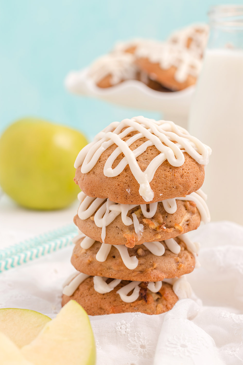 Stacked apple cookies with glaze and an apple in the background.