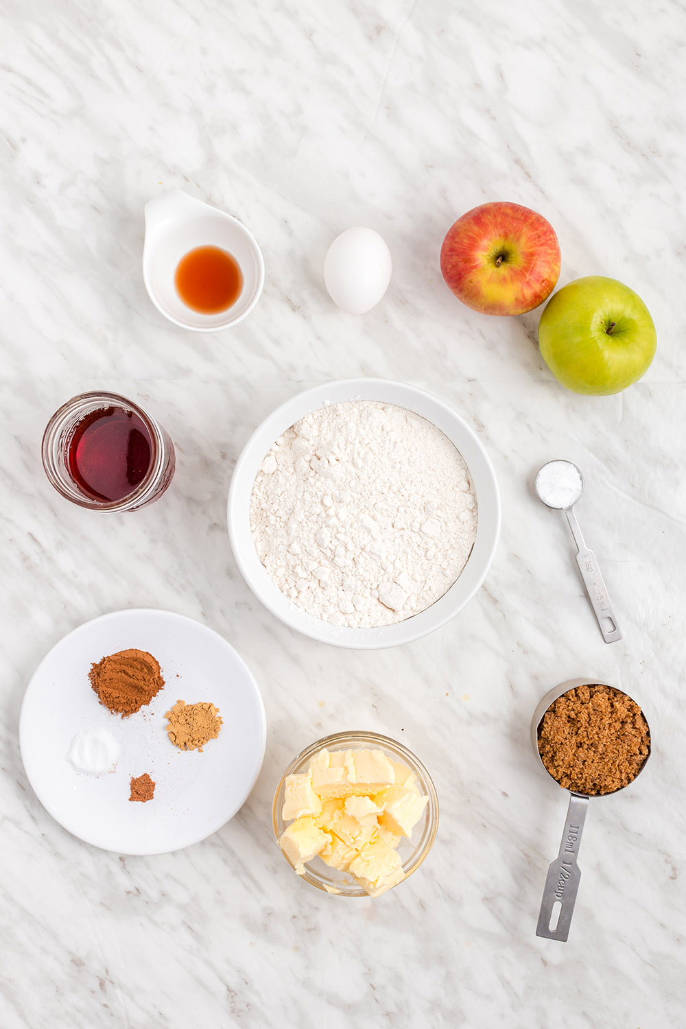 Apples, flour, cinnamon, and other ingredients on a table.