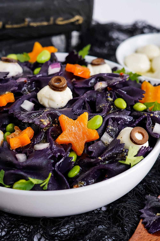 Star peppers and mozzarella eyeballs on top of black bat pasta for Halloween.