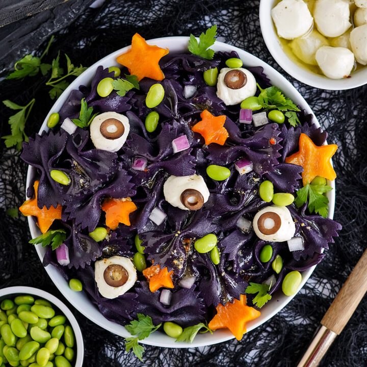 Bowl of bat pasta salad on a table surrounded by ingredients.