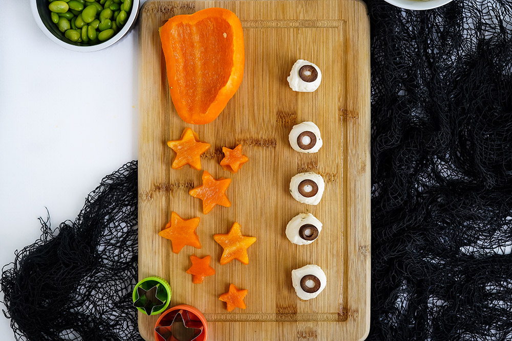 Cut peppers into star shapes and making mozzarella balls that look like eyeballs with olives.
