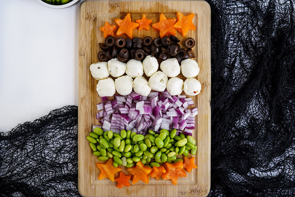Rows of chopped ingredients for pasta salad on a cutting board.