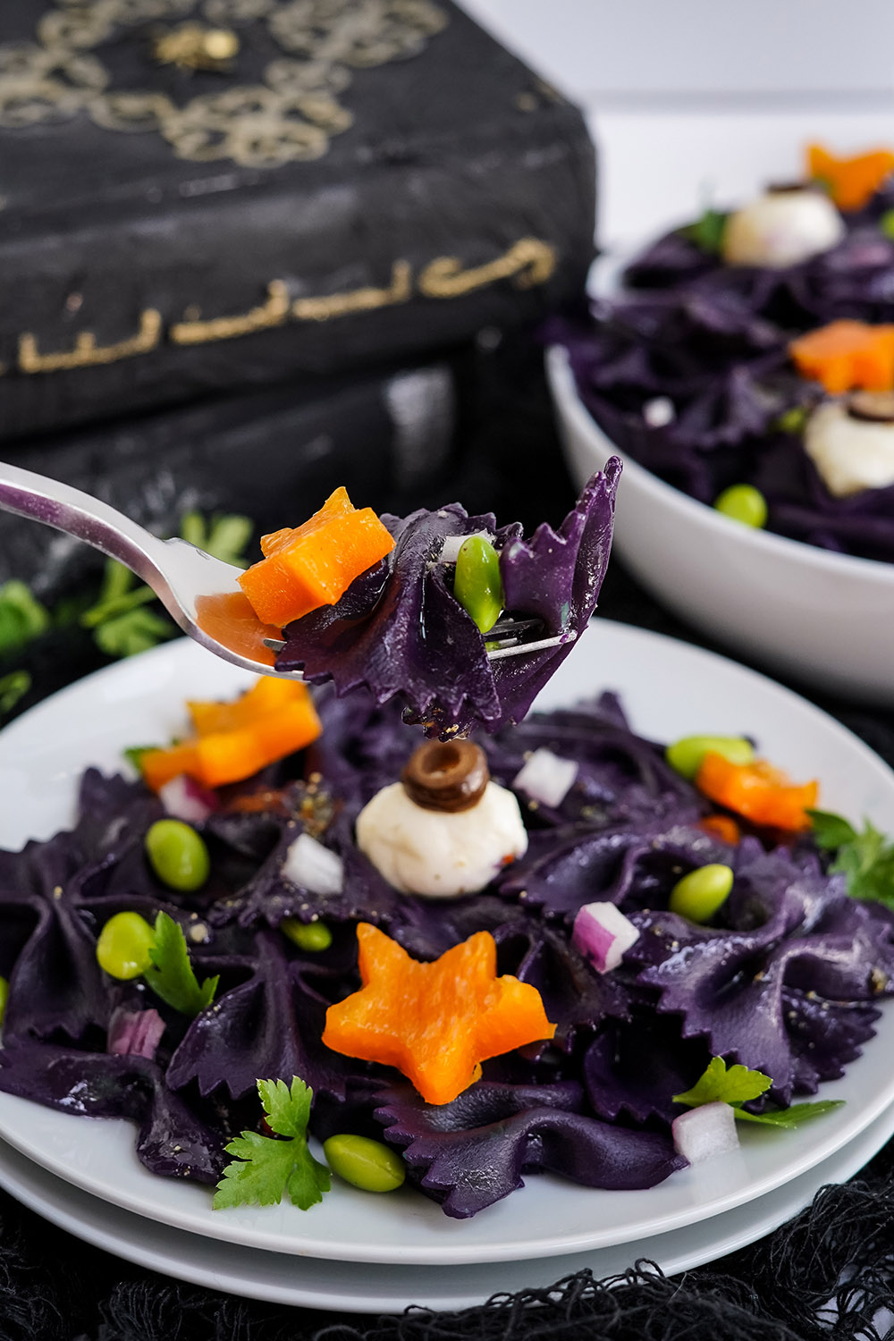Forkful of black pasta salad with the bowl in the background.