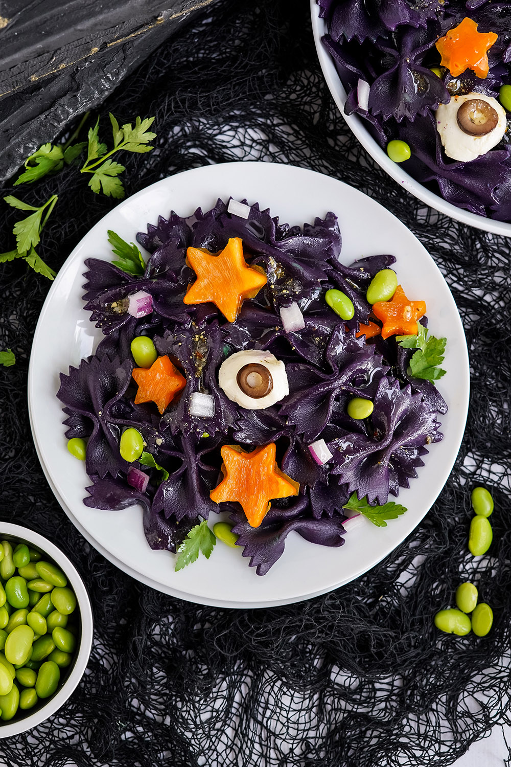 Overhead image of halloween pasta salad with bowls of ingredients on the table.