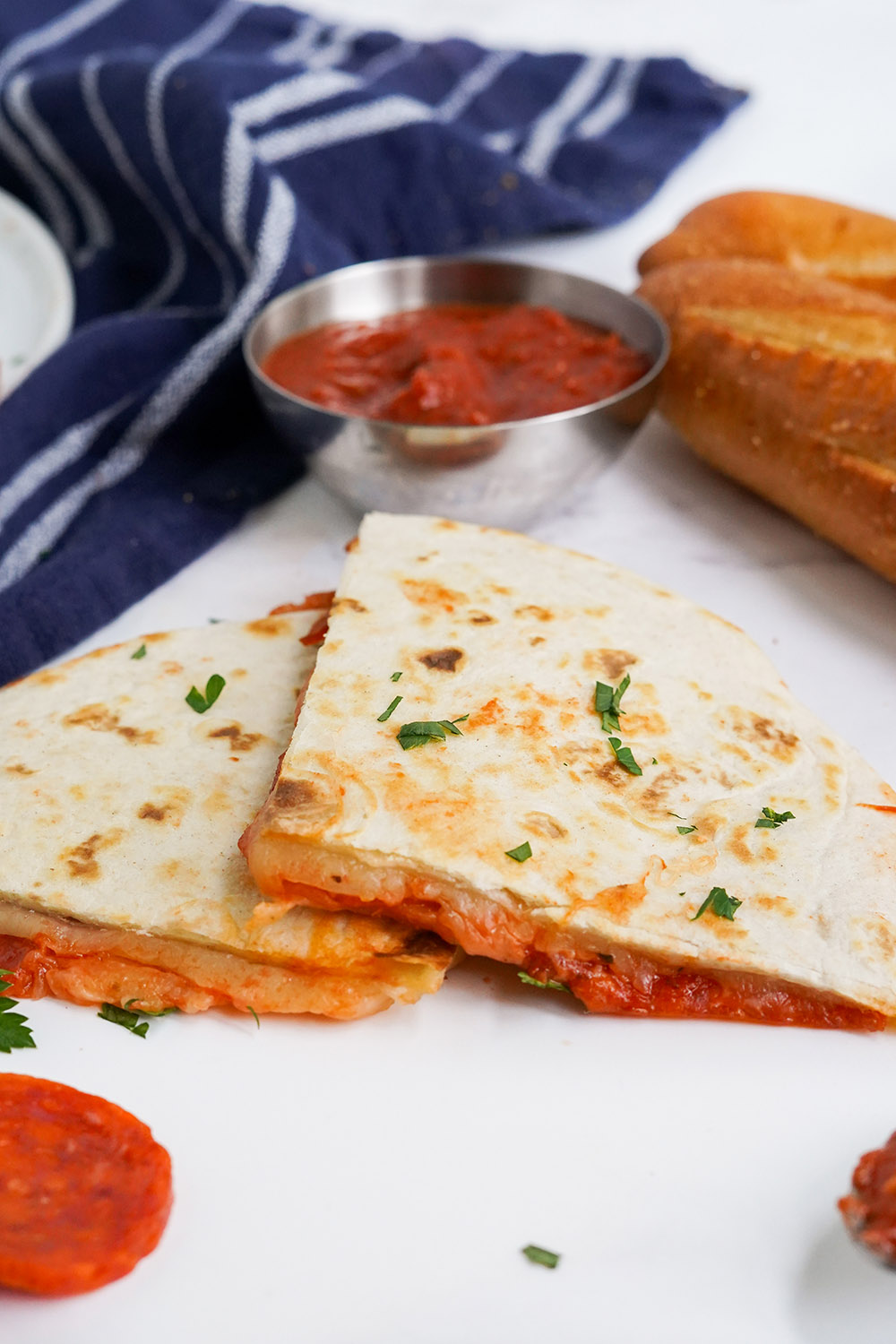 Two quesadilla slices on a table with dipping sauce.