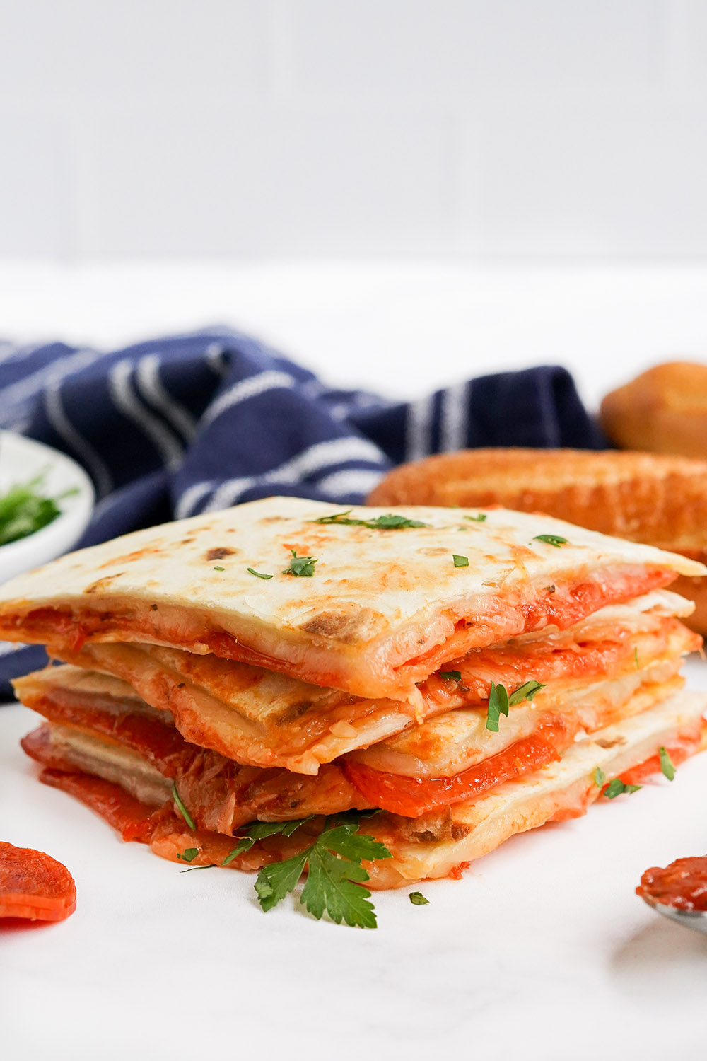 Stacked pizza quesadillas with parsley and a blue napkin.