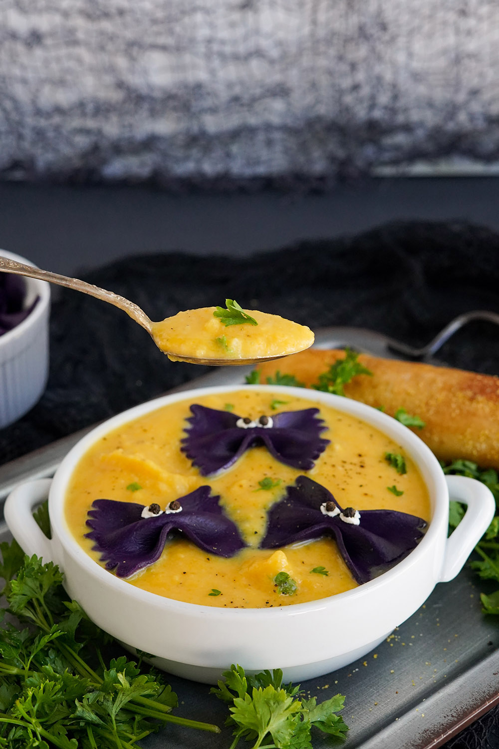 Raised spoon with butternut squash soup with bowl in the background.